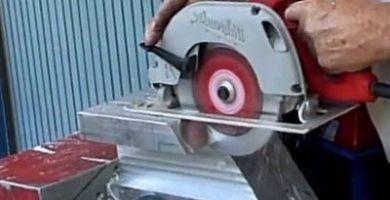 Una persona cortando aluminio con una sierra electrica